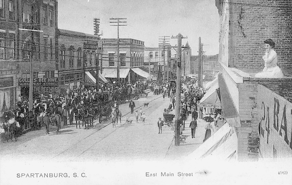 . In this 1904 photo from Spartanburg, South Carolina, a large crowd is gathered on the first block of East Main Street, while a woman overlooks the scene from the roof of a nearby two-story building.