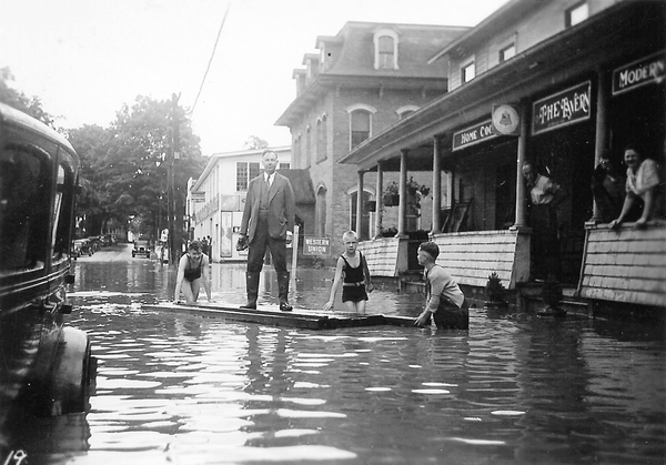 In this 1935 photo, residents of Groton, New York stand in a flooded Main Street, which was frequently inundated with water by the nearby Owasco Inlet.