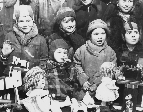 The purpose of most holiday windows was, above all, to sell more of a store's product. In many cases, stores would simply feature the newest toys they had for sale in their streetside windows, for children to point out to their parents. This 1936 photo shows a group of children looking at the new toys at F.W. Woolworth's, several of which were drawn from popular culture, such as Shirley Temple, or Popeye the Sailor Man.
