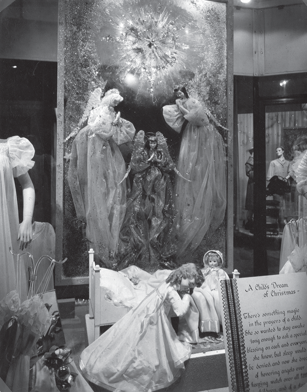 """Religious-themed windows were very popular with many companies, especially during the early-to-mid 1900s. This 1950s Christmas window is Neusteters' shows a """"Child's Dream of Christmas,"""" complete with heavenly angels.."""
