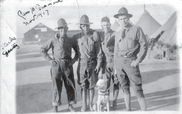 Four soldiers stand with their adopted dog in 1917.