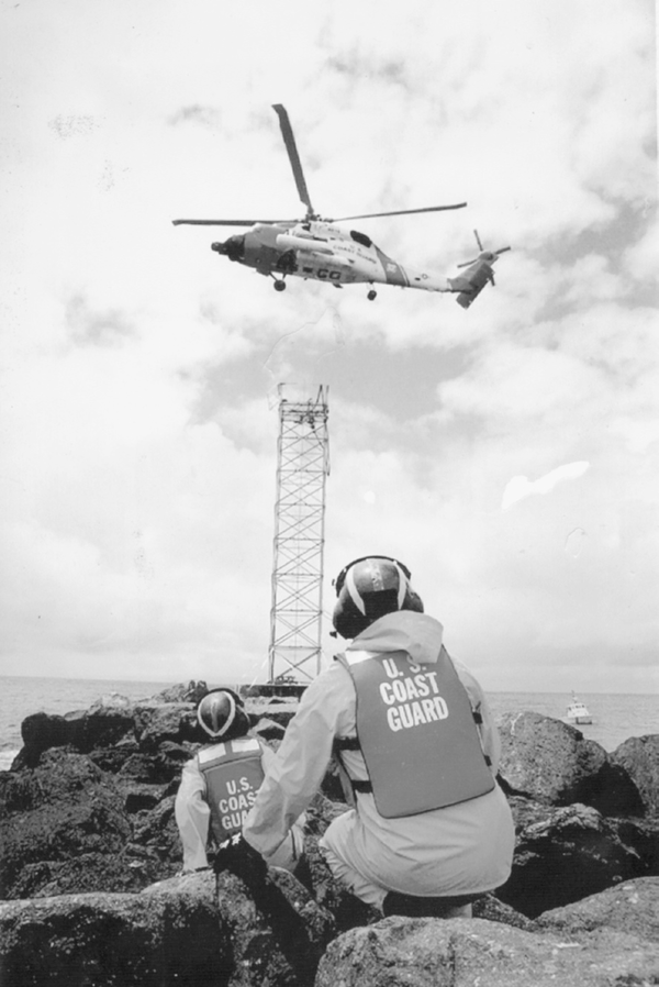A Coast Guard team delivers a battery to a south jetty near Mission Bay, in San Diego.