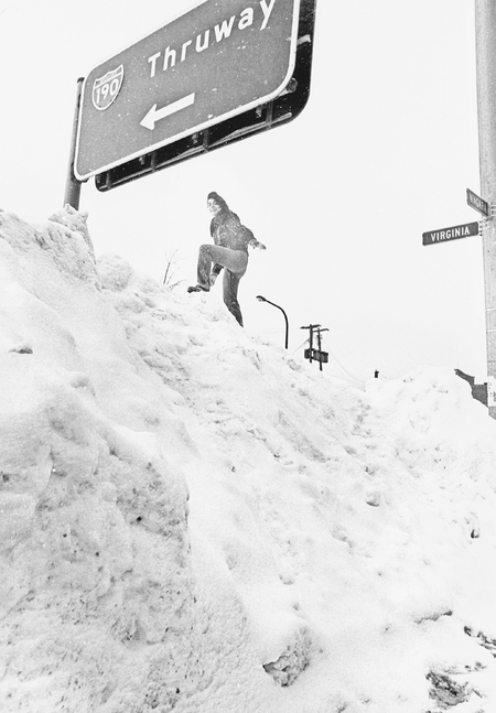 A young woman attempts to reach a highway sign during the Buffalo blizzard of 1977.