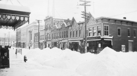Another New York snowstorm blanketed Sidney, New York. Here, snow piles are pushed in an attempt to clear the sidewalk.