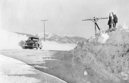 Children nearly reach the electrical wires on a snow bank in Crested Butte, Colorado.