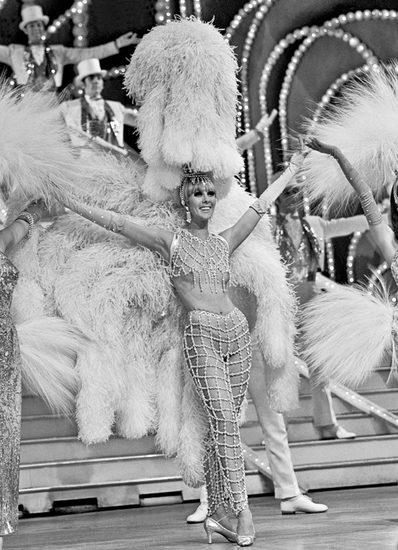 "This showgirl is pictured in 1968 during the Folies Bergere finale number titled ""Lumières de Paris."" The Las Vegas Sun newspaper describes the 1968 edition of the Folies Bergere as a ""dazzler"" and ""a contrived pastiche of richly costumed men and women."" (Courtesy of John Cook/Las Vegas News Bureau.)"