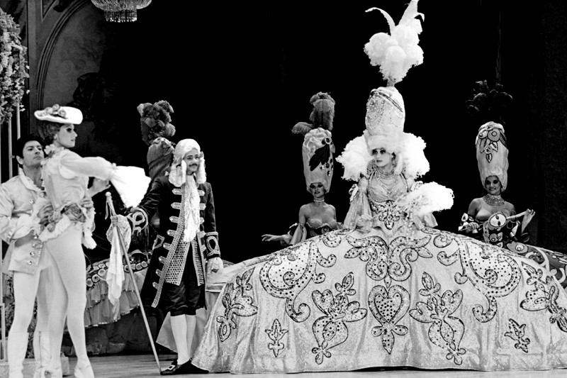 """Une Nuit à Versailles"" is the title of a scene from the 1980 ""revision-edition"" of the Folies Bergere that imagined the life of Marie Antoinette, the queen of France, during an evening with the royal court at the Palace of Versailles. The immense costume seen in this photograph measures nearly nine feet in width. With eight of this type of costume onstage at once, Folies Bergere creative director Jerry Jackson jokes that the proceedings backstage were as entertaining, if not more so, than the onstage performance. Thwarting collision between members of the dressed cast required meticulous choreography that was especially crucial during performers' entrances and exits. Seen in the front row of this photograph are, from left to right, Aleco Balsas, Terri Martin, William Garbett III, and Lydia Farrington-Jenkins. (Courtesy of UNLV Libraries Special Collections.)"