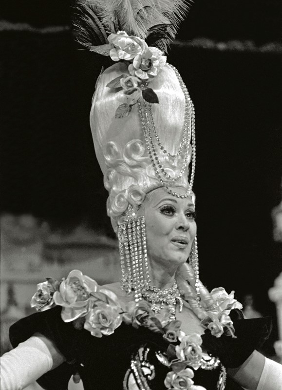 "This photograph dates from the 1971 edition and features Carolynn Everette as seen in the number titled ""Reception Chez Napoleon III."" Her costume, including the impressive ""pouf"" headdress, was designed by Michel Gyarmathy and represents a reliable theme employed in the cabaret genre that exploits visually significant historical fashion trends. A favorite historic era of the Folies Bergere was 18th-century France. The show's various creative teams staged acts depicting the French royal court at the Palace of Versailles in at least three separate editions of the production. (Courtesy of Gary Angell/Las Vegas News Bureau.)"