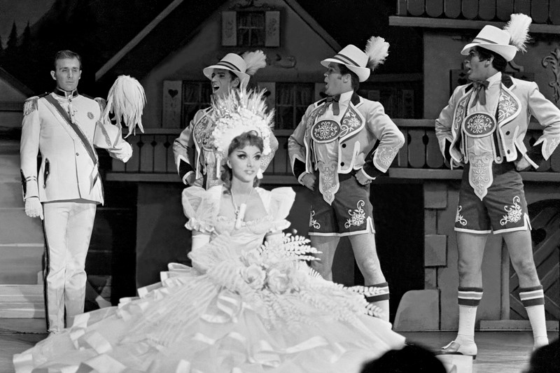 "Michel Gyarmathy's Tyrolean folk costumes and set backdrops for ""Marriage au Tyrol"" were charming and convincing adaptations of the traditional. Showgirl Fabiola is pictured in 1969 and costumed as the Tyrolean bride; at left is singer Bill De Bell. (Courtesy of John Cook/Las Vegas News Bureau.)"