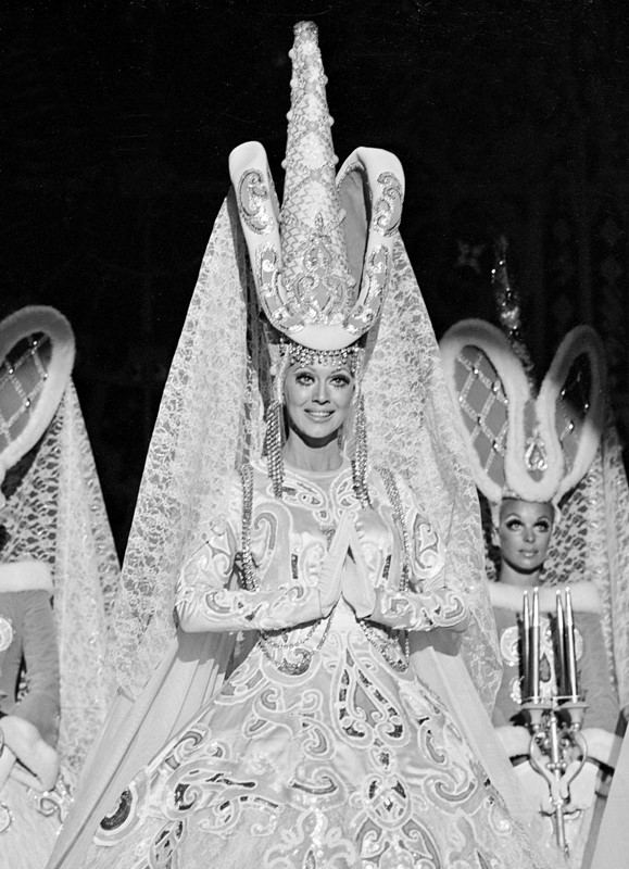 "This image was taken in 1972 during the scene titled ""Cathedrale"" and features principal performer Carolynn Everette (center) wearing a magnificent Gothic character costume designed by Michel Gyarmathy. Set pieces inspired by the stained-glass window designs of French cathedrals completed this fantasy set in the middle ages. The scene cleverly injected a note of piety into an otherwise sensual presentation. Such witty absurdities are inherent to the spirit of the musical revue. Gyarmathy describes the foundational template for every edition of the Folies Bergere as ""Always a cocktail: something sweet, something sour, something strong, and something effervescent."" (Courtesy of John Cook/Las Vegas News Bureau.)"