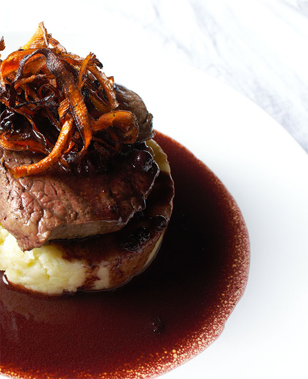 Elk tenderloin with huckleberry demi-glace – elk is native to the Montana area, as are huckleberries. Reprinted from The Big Sky Bounty Cookbook: Local Ingredients and Rustic Recipes by Chef Barrie Boulds and Jean Petersen, courtesy of Chef Barrie Boulds (pg. 109, The History Press, 2018).